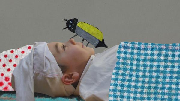 Ein Junge als Onkel Fritz verkleidet liegt mit seiner Schlafmütze im Bett. Auf seiner Nase krabbelt ein großer Maikäfer aus Papier. | Rechte: KiKA