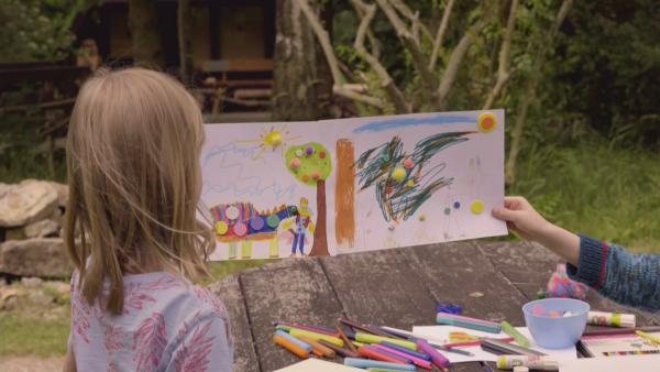 Zwei Kinder schauen sich ihr buntes, selbtsgemaltes Märchenwaldbild an. Auf dem Bild ist ein Prinz mit einem Drachen zu sehen. | Rechte: KiKA