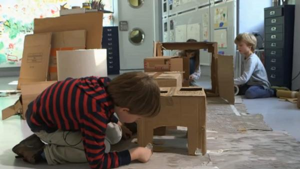 Drei Kinder bauen aus alten Pappkartons eine kleine Wohnung nach mit einem Herd und einem Kühlschrank. | Rechte: KIKA