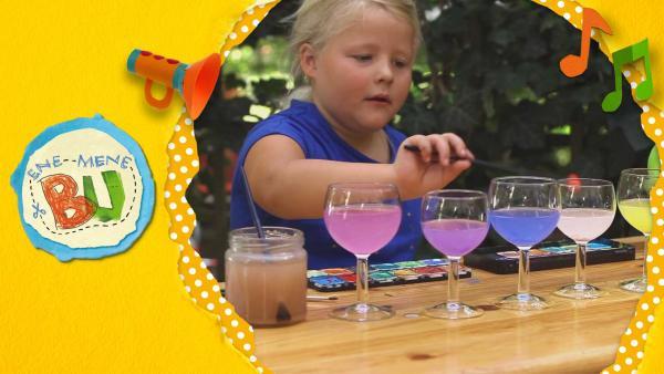 Nunu klopft mit einem Pinsel an Weingläser, die mit farbigem Wasser gefüllt sind und macht so Musik. | Rechte: KiKA