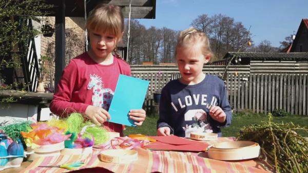 Elena und Rosalie basteln aus alten Käseschachteln ein Osternest und färben Osterier. | Rechte: KiKA