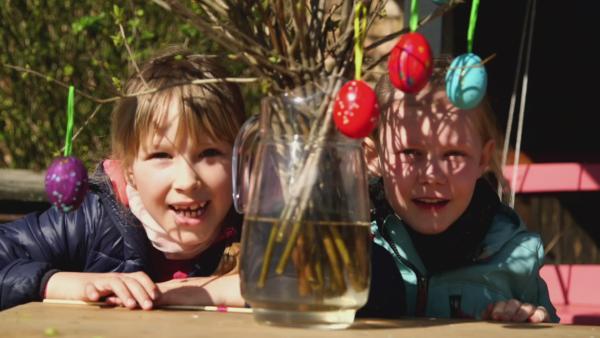 Elena und Rosalie schauen ihren Osterstrauß an. Diesen haben sie mit selbstbemalten Ostereiern dekoriert. | Rechte: KiKA