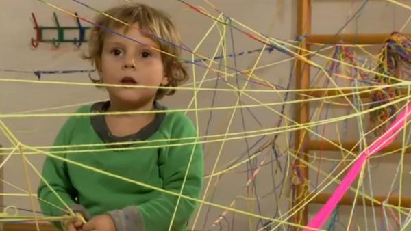 Als Beschäftigungsidee hat ein Kind bunte Fäden kreuz und quer durch einen Raum gezogen und verknotet. Es sieht aus wie ein großes Spinnennetz. | Rechte: KIKA