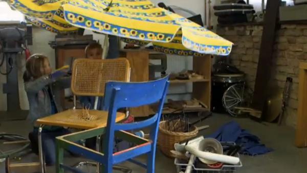 Upcycling-Idee für Kinder: Zwei Kinder bauen aus alten Stühlen, einem kaputten Sonnenschirm und anderen alten Gegenständen eine neue Maschine. | Rechte: KiKA