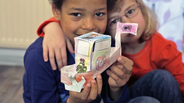 Zwei Kinder stecken ihr bunt bemaltes Steckboot aus Papier zusammen. | Rechte: KiKA