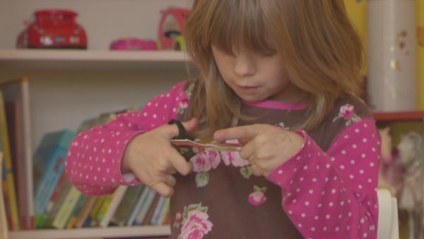 Ein Mädchen schneidet die Teile für die ENE MENE BU-Steckkatze aus. | Rechte: KiKA