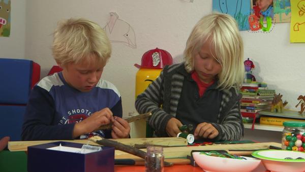 Casper und Linus bauen aus Kronkorken, Draht und einem Stock eine Rassel. | Rechte: colourbox.com