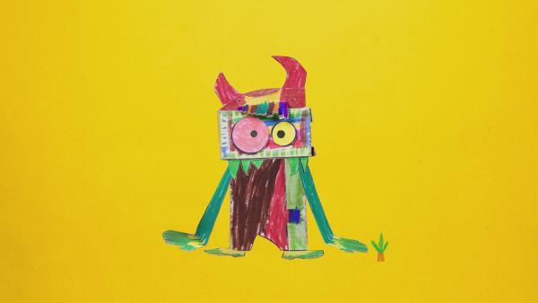 Ein Monster mit grüner, brauner und roter Farbe steht auf einer Wiese und isst Karotten.  | Rechte: KiKA