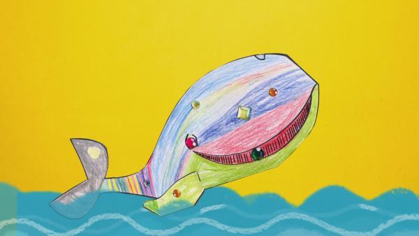 Ein bunt gestreifter Steckwal ist mit Glitzersteinen verziert. Der Wal springt gerade aus dem welligen Wasser. | Rechte: KiKA