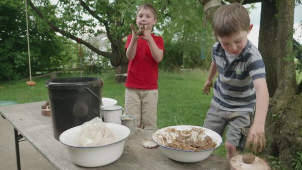 Sebastian und Lorenz formen Samenkugeln selber aus einem Gemisch aus Erde, Samen, Lehm und Wasser. | Rechte: KiKA