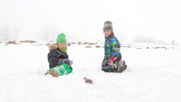 Josef und Elias lassen den ersten Bobfahrer ihre selbstgebaute Bobbahn runterfahren. Der Fahre rist eine Spielzeugfigur. | Rechte: KiKA