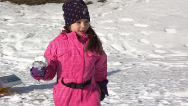 Ein Mädchen in einem pinlen Schneeanzug hat einen Schneeball in der Hand. | Rechte: KiKA