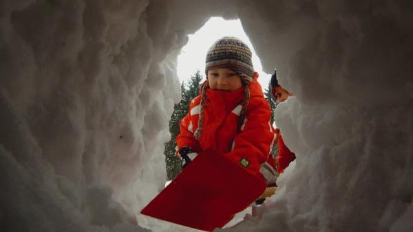 Ein Junge gräbt mit einer Schneeschippe ein Loch in einen Schneehaufen. | Rechte: KiKA