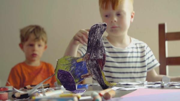 Ein mit Buntstiften angemalter Steckotter in den FArben schwarz, lila und gelb steht auf dem Schreibtisch von Oskar und Gregor. | Rechte: KiKA