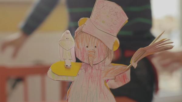 Ein mit Buntstiften angemealter Steckschneemann von ENE MENE BU mit einem Besen im Arm und einem Raben auf dem anderen Arm. | Rechte: KiKA