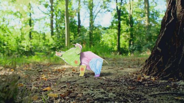 Ein bint bemaltes Steckschwein läuft steht im Wald auf herbstlichem Waldboden. | Rechte: KiKA