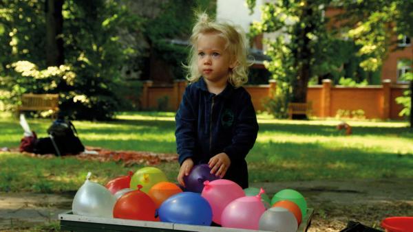 Hektor steht vor eine Kiste. In der Kiste sind viele bunte und mit Wasser gefüllte Luftballons. | Rechte: KiKA