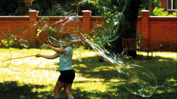 Hedwig macht mit zwei Stöcken und einem Seil dazwischen große Seifenblasen, einige zerplatzen bereits. | Rechte: KiKA