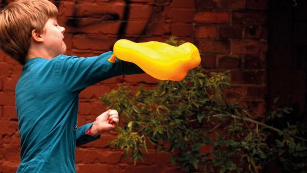 Jannis zerplatzt mit seinen Händen eine Wasserbombe. In der Zeitlupe sieht man, wie sehr sich der Luftballon verformt. | Rechte: KiKA