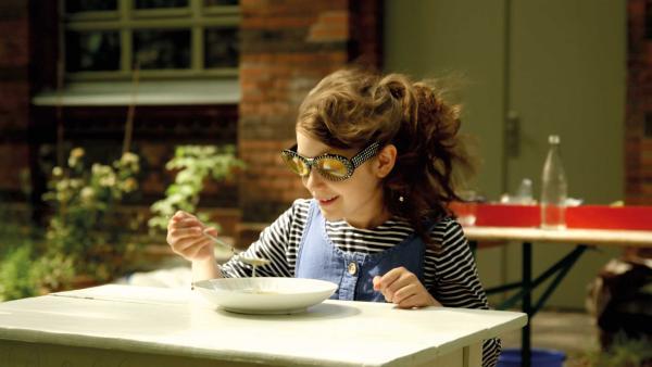 Ava versucht bei sehr starkem Wind eine Suppe auszulöffeln. | Rechte: KiKA