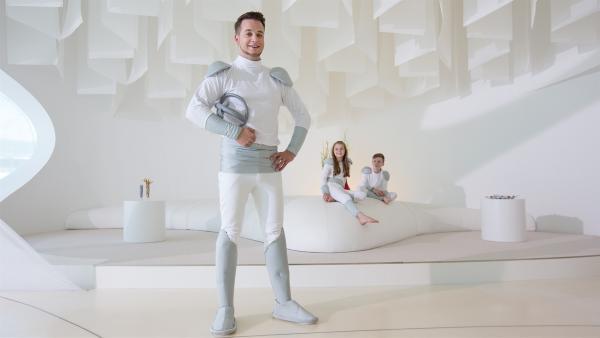 Felix mit Beamhelm, im Hintergrund die Schauspieler-Kinder Finja und Florenz im futuristischen Wohnzimmer. | Rechte: KiKA/Stefan Lemanski