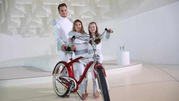 Felix und die Schauspieler-Kinder Mara und Finja begutachten ein Fahrrad aus dem Jahr 2016. | Rechte: KiKA/Stefan Lemanski