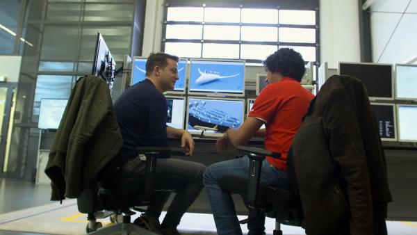 Luftfahrtingenieur Yasim Hasan zeigt Felix, wie weit die Forschung ist, das Fliegen umweltfreundlicher zu machen.   Rechte: KiKA