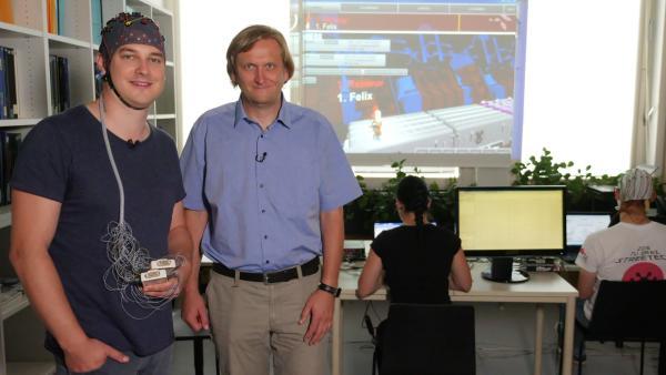 Felix mit Prof. Müller-Putz vor dem gedankengesteuerten Computerspiel | Rechte: KiKA/tvision/Martin Beume