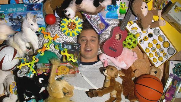 Was ist gutes Spielzeug? Und warum haben wir so viel davon? Felix sucht in Spielzeugkisten.  | Rechte: KiKA