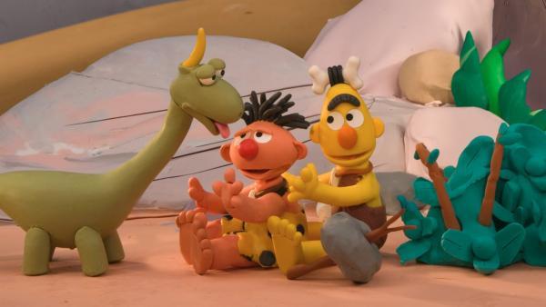 Ernie und Bert sind Höhlenmenschen und wollen für ihren Hausdino Spot eine Hütte oben auf einem Hügel bauen.   Rechte: NDR/Sesameworkshop