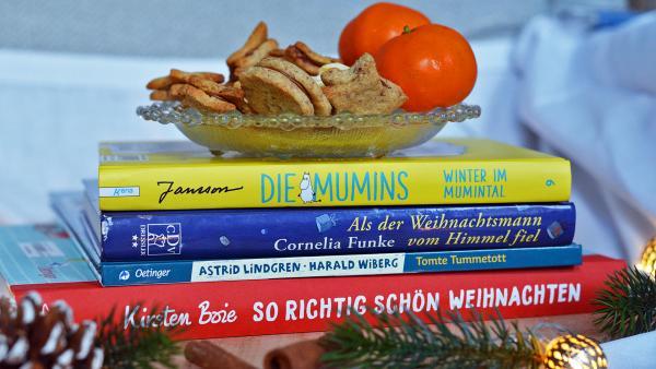 4 Bücher liegen übereinander gestapelt auf einem Holzbrett. So richtig schön Weihnachten von Kirsten Boie, Tomte Tummetott von Astrid Lindgren, Als der Weihnachtsmann vom Himmel fiel von Cornelia Funke und Die Mumins- Winter im Mumintal von Tove Jansson. Auf dem Bücherstapel steht eine Schale mit Plätzchen und Mandarinen. Vor dem Bücherstapel liegen Tannenzweige und Zapfen sowie eine Lichterkette. | Rechte: Karolin Rommeis