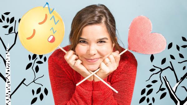 Anna zeigt einen müden und einen Herz-Emoji. | Rechte: BR/Text und Bild Medienproduktion GmbH & Co. KG