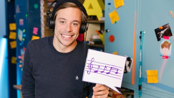 Tobi mit Kopfhörern und Musiknoten auf einem Papier in der Checker-Bude | Rechte: Hans-Florian Hopfner