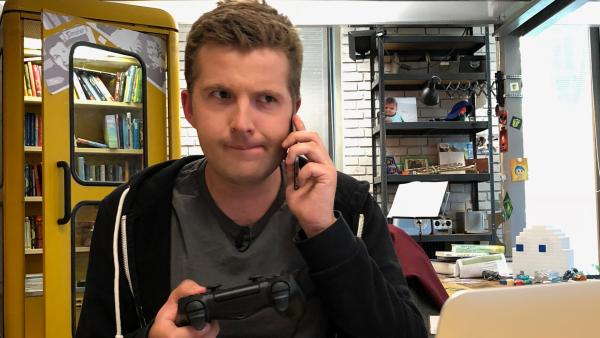 Tim mit einem Smartphone und einem Controler in der Hand. | Rechte: KiKA
