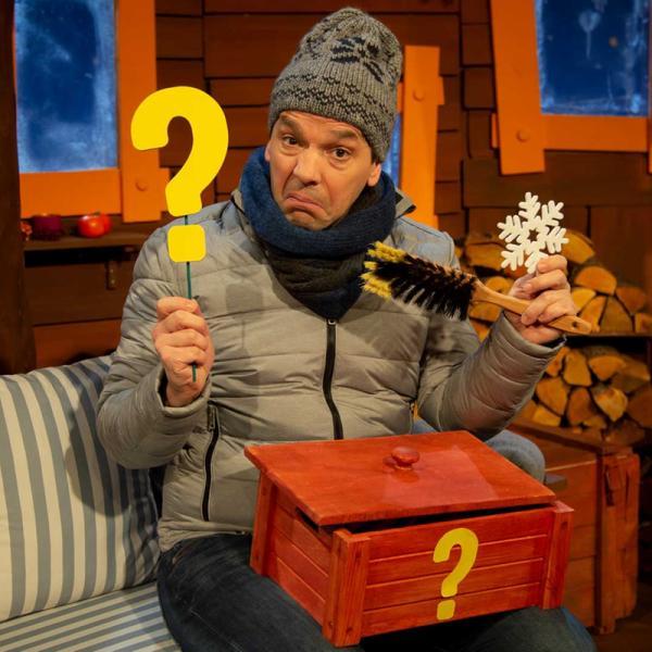 Juri Tetzlaff im KiKA-Baumhaus trägt eine Mütze, Schal und Jacke. Er hält ein gelbes Fragezeichen, einen Feger, ein Eiskristall und auf seinem Schoss liegt eine geöffnete, rote Kiste mit einem gelben Fragezeichen auf der Vorderseite. | Rechte: KiKA/ Nadja Usbeck