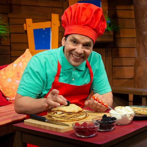 Juri Tetzlaff im KiKA-Baumhaus garniert Pfannkuchen mit Beeren und trägt eine rote Kochschürze sowie eine Kochmütze.  | Rechte: KiKA/ Josefine Liesfeld
