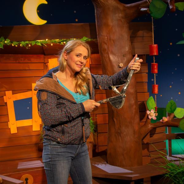 Singa Gätgens im KiKA-Baumhaus hält ein sonderbaren Alltagsgegenstand in den Händen. | Rechte: KIKA/ Josefine Liesfeld