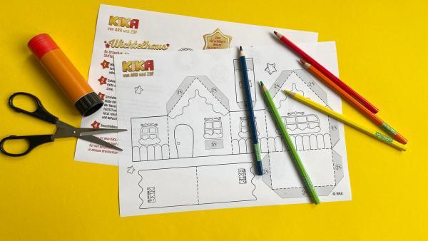 Wichtelhaus Bastelanleitung Schritt 2. Die Bastelvorlage mit Buntstiften, einer Schere und einem Klebestift. | Rechte: KIKA