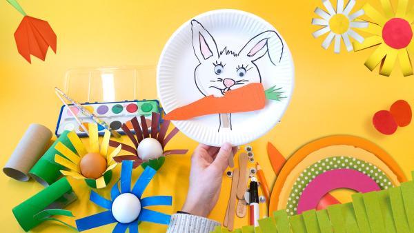 Gelbes Bild mit Bastelmaterialien. Darauf ist eine Hand zu sehen, die einen Pappteller hält. Auf dem weißen Pappteller ist ein Hase mit einer Möhre. Im Hintergrund sind ein Farbkasten und Eierbecher aus Klopapierrollen zu sehen. Das Bild ist hell und freundlich   | Rechte: KiKA
