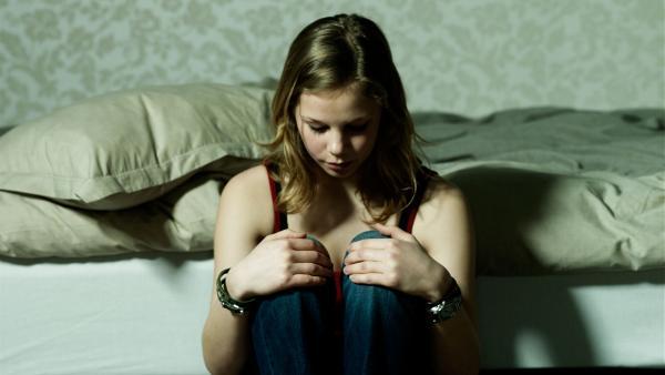 Ein Mädchen sitzt traurig an ihr Bett angelehnt. | Rechte: colourbox.com