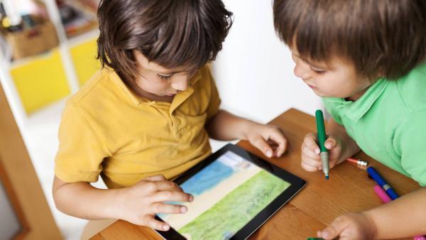 Zwei Jungen schauen auf ein Tablet, das auf dem Tisch liegt. | Rechte: IMAGO