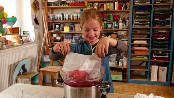 Ein Kind taucht ein Taschentuch in geschmolzenes Wachs und gestaltet so ein Wachstuch. | Rechte: KiKA