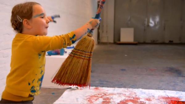 Kind schwingt einen Besen mit Farbe über einer Leinwand | Rechte: KiKA