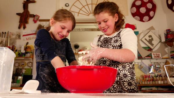 Zwei Kinder experimentieren mit Maisstärke und Wasser. | Rechte: KiKA