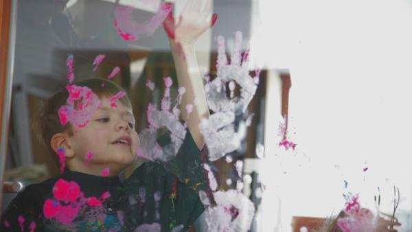 Kind druckt seine Hand mit Puddingfarbe an Glasscheibe | Rechte: KIKA