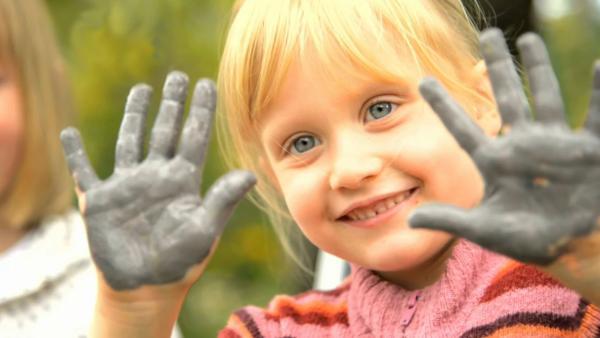Kind zeigt seine bemalten Hände | Rechte: KiKA