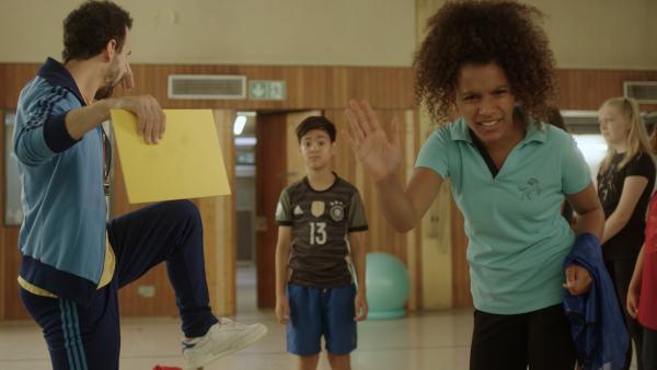 """Auf dem Bild ist im Vordergrund ein Mädchen, das die Hand zu einem """"Stopp""""-Signal hoch hält. Im Hintergrund sind weitere Jugendliche und ein Sportlehrer, die Leute stehen in einer Turnhalle.   Rechte: KiKA/Domenik Schuster"""