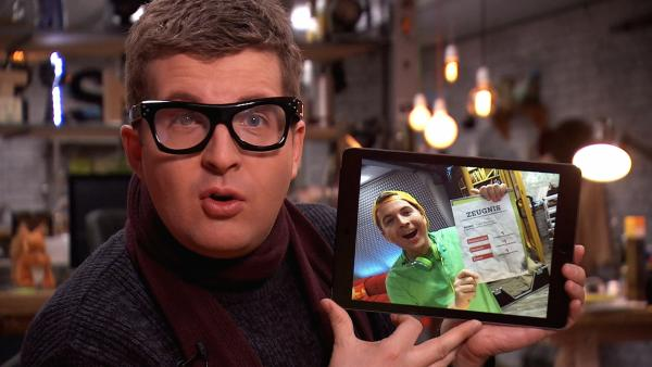 Tim verkleidet als Papa mit Foto auf dem Tablet | Rechte: KiKA