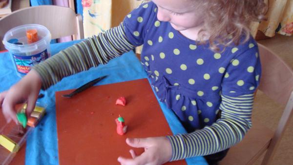 Ein Mädchen, das eine Figur aus roter Knete baut. | Rechte: KiKA