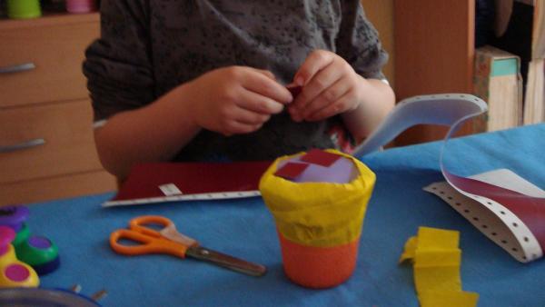 Kind beklebt die Rassel mit buntem Papier | Rechte: KiKA